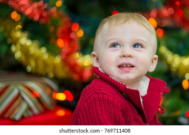A baby boy looks up and smiles while wearing a red sweater. It is Christmas morning and the infant sits next to a decorated Christmas tree and wrapped presents.