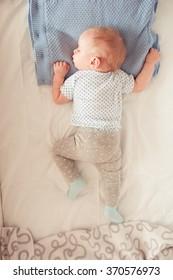 Baby boy lying in bed. Top view. Kid sleeping in room. Childhood. Bedtime. Healthy lifestyle.