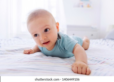 Baby boy lying on bed on his stomach and exercise to hold his head up