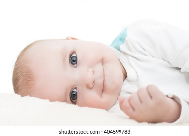 Baby boy lying on a blanket,white background.He is looking at camera.