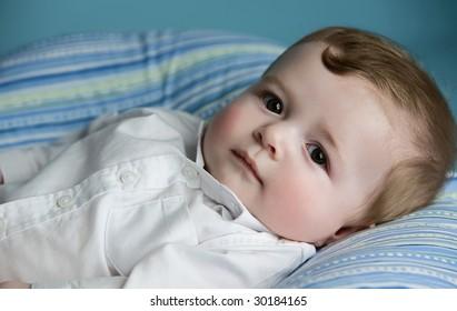 baby boy lying on pillow