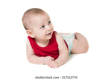 baby boy lying on a white background, wearing a diaper looking up smiling