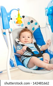 Baby boy in a musical swing home against white background