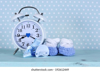 Baby boy nursery blue and white booties and clock, on aqua vintage shabby chic wood table and polka dot background for baby shower or newbornl greeting card.