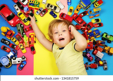 Baby boy on multicolored background surrounded by toy cars,top view