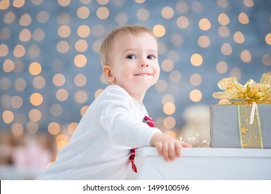 Baby boy one year old in white pajamas and tie takes the first steps and first successes, climbs the stairs. Large portrait