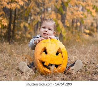 Baby boy outdoors with real halloween pumpkin