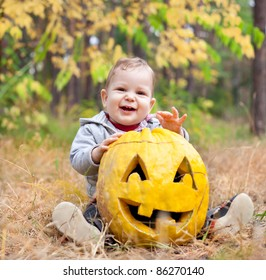 Baby boy outdoors with real pumpkin carved Jack O Lantern