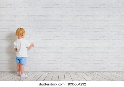 Baby boy with paint brush standing back near brick wall