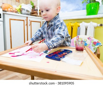 Baby boy painting with watercolors. Small caucasian child playing in home with paint and brush