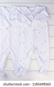Baby boy pajamas sleepwear. White clothes for kids on wood, top view.