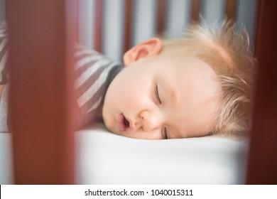 Baby boy peaceful sleeping in his crib.