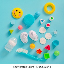 Baby boy personal accessories, top view on pastel background. Newborn infant care products and toys in flat lay arrangement.