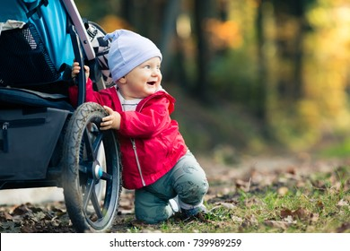 Baby boy playing in autumn forest with stroller, outdoors fun. Happy child on hiking trip in woods.
