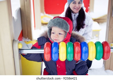 baby boy playing with his mother on a winter playground