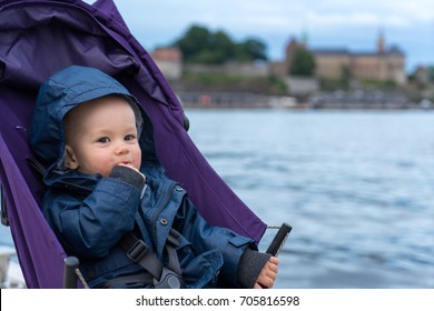 Baby boy playing in his stroller in central Oslo, Norway. (1y old)