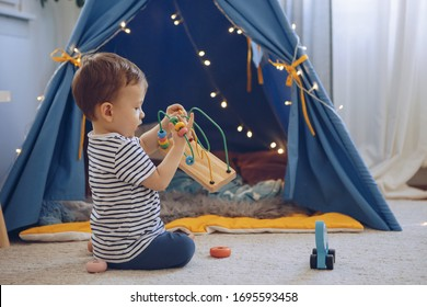 Baby boy playing with his toys in front of tent in living room