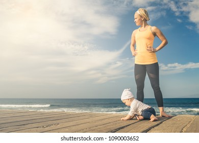 Baby boy playing with mother on the beach, summer day. Supermom with toddler son learning to walk on wooden beach sidewalk.