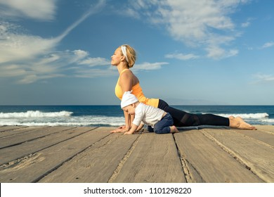 Baby boy playing with mother on the beach, summer day. Supermom with toddler son learning yoga on wooden beach sidewalk.