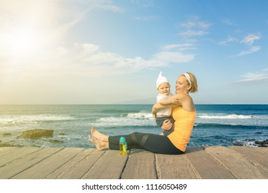 Baby boy playing with mother on the beach, summer day. Supermom with toddler son relaxing on wooden beach sidewalk. Looking at inspiring landscape.