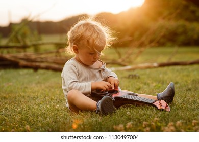 Baby boy is playing on the guitar toy on the grass in the sunset with blurred background.