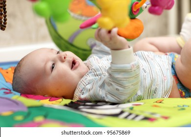 The baby boy playing on a mat at home