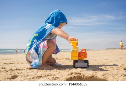 Baby boy playing on sand at the beach with excavator toy. He is wearing hooded poncho towel
