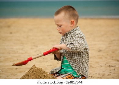 baby boy playing on the sand beach, dressed in shirt and shorts, sea background, playing with sand and beach toys.Playing with red plastic trowel.