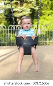 Baby boy playing on the swing in the park