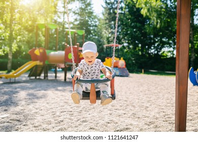 Baby boy playing in playground area. Portrait of smiling toddler looking at camera with happy face, having fun. Swaying on sunny summer day outdoors.