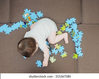 Baby boy playing with puzzle pieces on a sofa at home