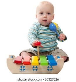 A baby boy playing with a rattle and a xylophone.  Isolated on white.