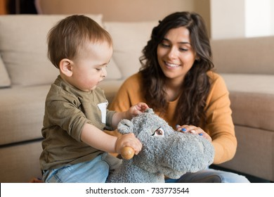 Baby boy playing with a rocking horse with mom's help