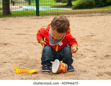 Baby boy playing with sand