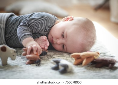 Baby boy is playing with the teddy bears on the carpet with blurred background.