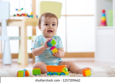 baby boy playing toys in nursery or daycare