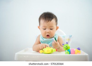 baby boy playing with toys on high chair,fun baby,asian baby