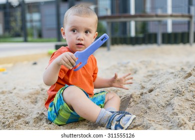 Baby boy playing with toys in sandpit playground