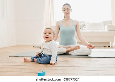 Baby boy playing with toys while his mother meditating at lotus position.