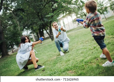 Baby boy playing water guns with young hipster parents in park in summer outdoors