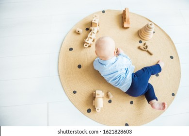Baby boy playing with wooden toys lying on the Mat. Ecology, education, upbringing concept