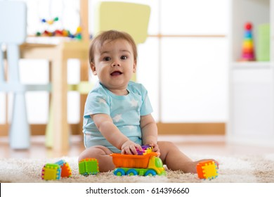baby boy playing wooden toys at home or kindergarten