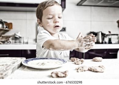 Baby boy preparing meatballs. He is kneading the balls