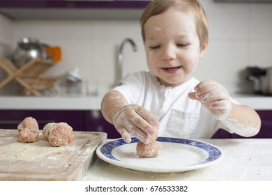 Baby boy preparing meatballs. He is playing with just kneaded meatballs