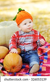 baby boy with pumpkins on a background of yellow foliage