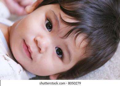 Baby boy quietly looking at camera, slightly sleepy expression.