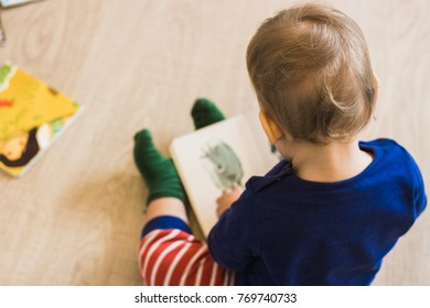 Baby boy reading books at home