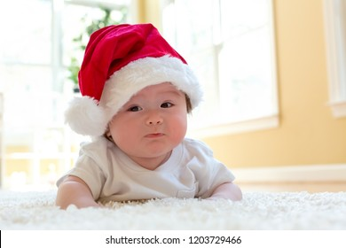 Baby boy with a Santa hat on Christmas morning