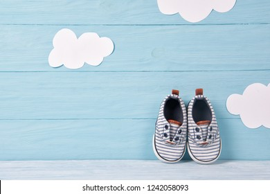 Baby boy shoes on a blue wooden background with clouds