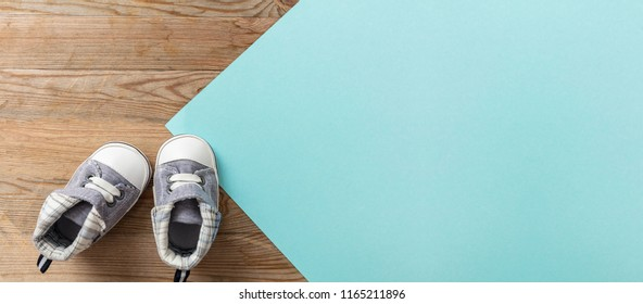 Baby boy shoes, shower invitation concept, on pastel blue and wooden background, banner, copy space, top view